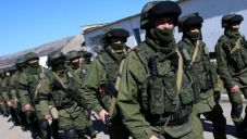 Masked servicemen march near the checkpoint of the 36th separate brigade of the Ukrainian Navy coastal defense at the Perevalnoe base in Crimea. (PressTV)